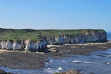 En rad vita klippor toppade med grönt gräs som sticker ut i havet.