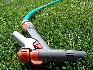 Garden hose - Sprayer pistol uses a quick-connect fitting, visible just beyond the sprayer grip