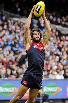 Jeff Garlett catching a yellow football above his head