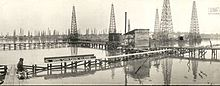 A black-and-white photograph showing a field of oil derricks and thin wooden boardwalks built over the water.
