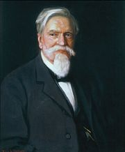 A color portrait of an older gentleman with white hair and a white goatee