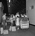 Groep reizigers met een kar vol bagage te wachten in een hal bij de douane, Bestanddeelnr 255-2206.jpg