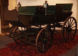 Fyrhjulig vagn med säte längs sidorna