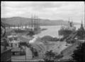 """Harbour scene, probably at Port Chalmers, with several ships berthed at the wharves including the steel 4 masted barque """"Olivebank"""" ATLIB 292537.png"""