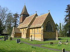Yellow stone building with red tiled roof and square tower with short spire. Foreground is grass with gravestones.