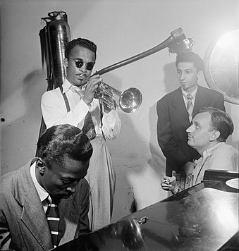 Davis on piano with Howard McGhee (trumpet), Joe Albany (pianist, standing) and Brick Fleagle (guitarist, smoking), September 1947 Howard McGhee, Brick Fleagle and Miles Davis, ca September 1947 (Gottlieb).jpg