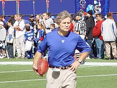 Candid photograph of McNally wearing a blue t-shirt bearing a New York Giants logo standing on a football field and holding a football in his right hand with his left hand on his hip