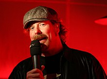 A 2008 photograph of actor John DiMaggio, speaking into a microphone
