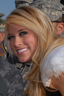 A close-up photo of a young, Caucasian blonde woman, who is smiling at the camera. Men in camouflage uniforms are visible in the background.