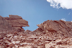 Longs Peak - The Keyhole as seen from the Boulder Field. A small stone shelter (Agnes Vaille Memorial) approximately 10 feet (3 m) high that sits on the left side of the Keyhole gives a sense of scale.