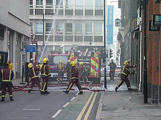 London Fire Brigade - LFB firefighters at a building fire; one uses an axe (right) to gain entry
