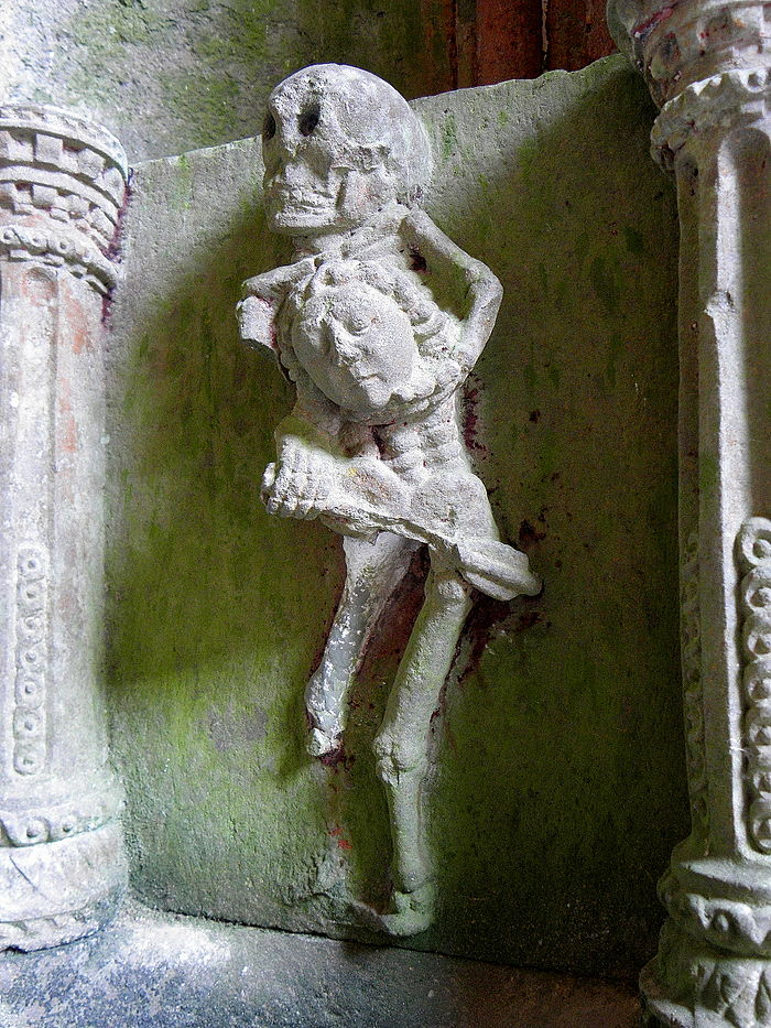"The stoup in the church porch with a depiction of the ""Ankou"" with arrow. He holds the head of a child.[2][6]"