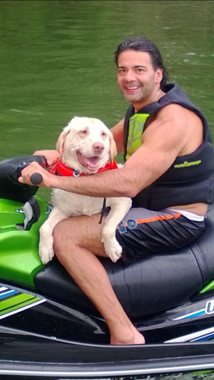Human–canine bond - A Labrador Retriever with his owner on a jetski