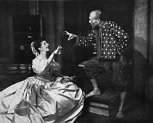 Woman kneeling in front of a standing man; the two are conversing amiably, and each is gesturing with one hand as if ringing a small bell, although, according to the song lyrics, they are actually demonstrating the flying motion of a honey bee