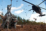 Leaves and twigs are whipped into the air by the rotor wash of UH-60 Black Hawk helicopter as soldiers prepare to hook up an M119A2 105mm howitzer during air assault training at Fort Bragg, N.C., on Feb 130208-A-3108M-006.jpg