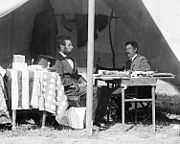 Photograph of Lincoln and McClellan sitting at a table in a field tent