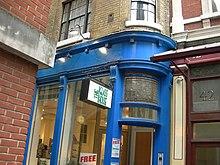 """Een blauw geverfd gebouw, met een bord met de tekst """"The Glass House"""".  Op de deur is een advertentie op een bril aangebracht."""