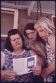 MRS. MAY WATKINS, DAUGHTER, BERTHA, CENTER, AND A PLAYMATE LOOK OVER A RELIGIOUS PAMPHLET JUST LEFT AT THEIR NEW... - NARA - 557364.tif