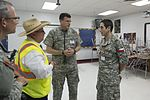 Maj. Enrique Romero, a physician in the Chilean Air Force, discusses medical operations with Col. Jonathan MacClements, Texas State Guard.jpg