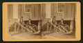 Man seated in a wooden wheelchair, by J. F. Kennedy.png