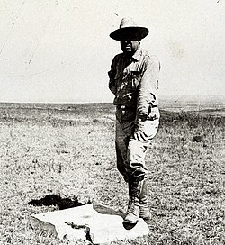 Man standing with one foot on concrete block with metal disc in center