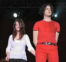 The White Stripes standing on stage: Meg Whi is to the left, wearing a white shirt and black pants, smiling at the crowd; to her left is Jack White wearing a red outfit with a black belt
