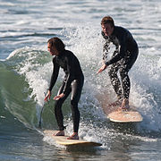 Two surfers wearing one-piece wetsuits, riding a wave.