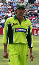 A dark coloured man wearing light green outfit and dark coloured cap. Cricket field and spectators can be seen in background.