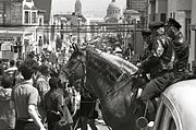 A pair of policemen mounted on horses observe a protest march down a street in San Francisco.