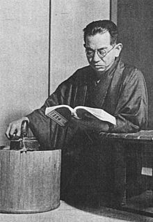 A middle-aged Japanese man, wearing a kimono and glasses, in a kneeling position, is reading a book he holds in his left hand, his elbow resting on a table, while his right hand rests upon a tea kettle