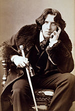 Photo of Wilde with long hair, cane and bearskin coatr