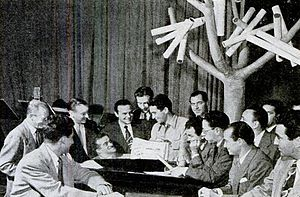 "Perry Como - Como meeting with songwriters' representatives in the ""Supper Club"" studio. He met with the ""song pluggers"" every Wednesday following the West Coast broadcast of Chesterfield Supper Club."