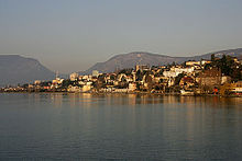 A collection of houses and other small buildings scatter the shore of a wide lake