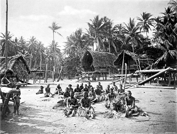 Black and white photograph of people sitting in a wide, open area in a village.  A forest of palm trees fills the background.