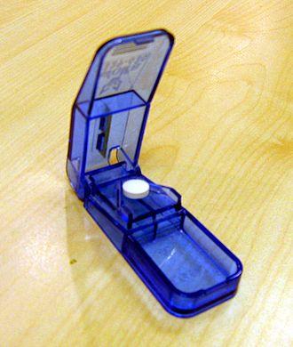Pill splitting - A pill-splitter holding a tablet ready to split.