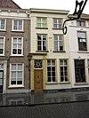 foto van Huis met gebosseerd witgepleisterde lijstgevel, ingang met geblokte pilasters en kroon- en tandlijst en in een cartouche de spreuk: beziet u eerst zelven 1649