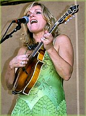 A blonde woman in a green dress singing and playing the mandolin.