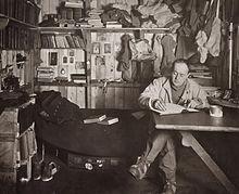 Man zit met gekruiste benen aan tafel, pijp in de hand, blijkbaar aan het schrijven.  Veel kleding, boeken en spullen staan op de achtergrond.