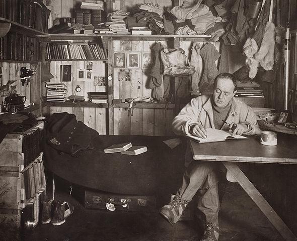 רוברט סקוט כותב ביומנו בבקתה שלו באנטארקטיקה (ויקיפדיה) - הפודקאסט עושים היסטוריה עם רן לוי