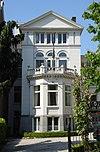 foto van Villa. Gepleisterde gevel met getoogde en rechthoekige vensters, driezijdig uitgebouwde erker met balconhek en bekronend fronton