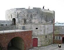 Fronto renkontante vidon de Round Tower de Portsmouth, kiu siatempe gardis la enirejon al Portsmouth Harbour. La Je Turo mem estas farita el ŝtono kaj havas grandan cirklan bazon.