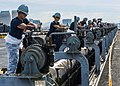 Sailors work together to lower a catapult track back into the flight deck USS Theodore Roosevelt. (29357574934).jpg