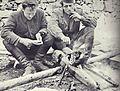 Saniteteni referent 14. divizije Stane Pirc in njegov pomočnik Albin Polk Fajfa ob ognju v taboru 14. divizije na Starih ogencah nad Leskovo dolinu v začetku novembra 1943.jpg