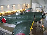 Color photo of a dark green single engined monoplane aircraft inside a room