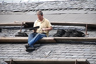 Roof pitch - Shingled roofs with pitches too steep to walk on require a staging of planks on roof brackets.  Slater at work, Rothesay, Isle of Bute
