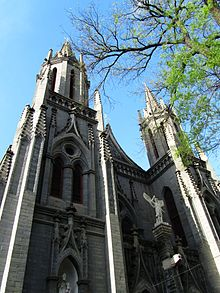 Two ornate spires of grey stone, with a tree branch partially in leaf at right, seen against a blue sky at a sharp upward angle