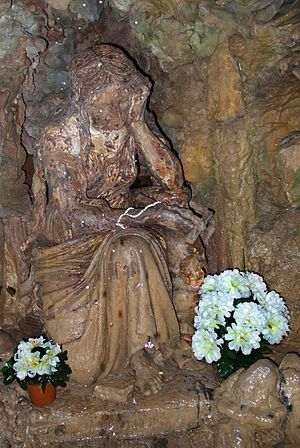 Baulou - Statue of Madeleine in an artificial cave. Note the skull beneath the crucifix in her hand.