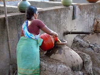 Feni (liquor) - Fermented cashew fruit juice being transferred into pots for distillation