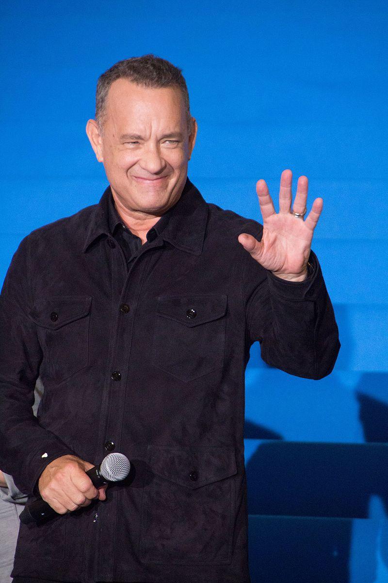 Tom Hanks saludando con un micrófono en la otra mano y un fondo azul para identificar a uno de estos 10 famosos y celebrities que usan CBD.