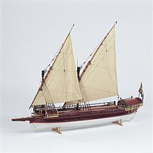 A side view of a model of a small galley with two masts rigged with lateen (triangular) sails. Its outrigger folded up and the oars stowed on the deck. The hull above the waterline is painted red with decorative details in gold and blue. The bow has a raised platform (rambade) armed with 3 small cannons.
